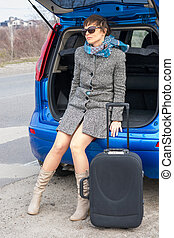 Young woman in sunglasses near the car with a suitcase