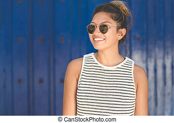 Young woman in sunglasses on blue background smiling