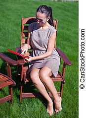 Young woman in sunglasses on chair outdoor looking at laptop