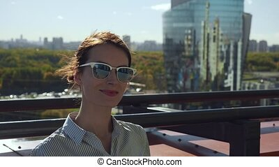 Young woman in sunglasses posing on commercial building balcony.