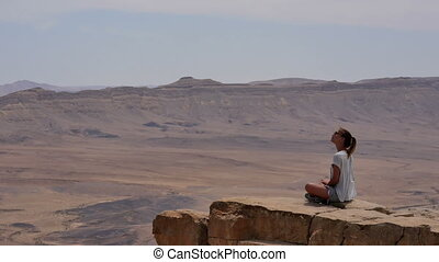 Young woman in sunglasses sitting on cliff's edge and looking around the desert