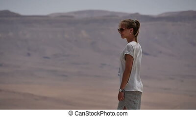 Young woman in sunglasses standing on cliff's edge and looking around the desert