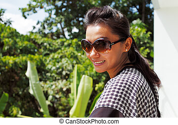 Young woman in sunglasses standing