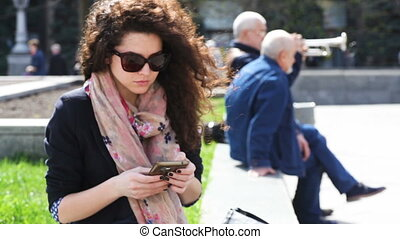 Young woman in sunglasses using smartphone outdoors