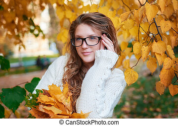young woman in sunglasses walking in autumn park