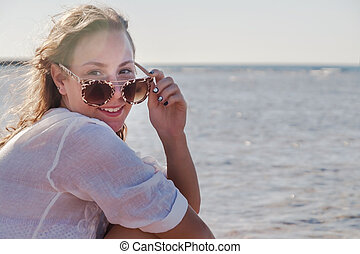 Young woman in sunglasses with developing hair, smiling. Concept of youth, summer, rest