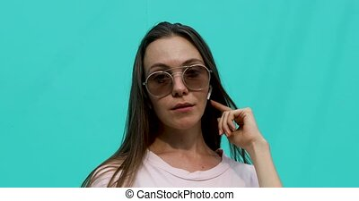 Young woman in sunglasses with earphones - Attractive...