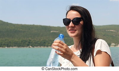 Young Woman In Sunglassrs Drinking Pure Water On a Background of Mountain Lake At Sunny Summer Day.