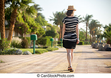 Young woman in sunhat, back view