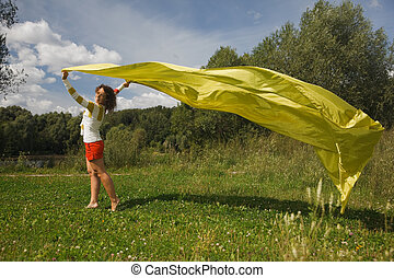 young woman in sunny summer day holds in a hand developing on a wind a yellow fabric. looking in camera