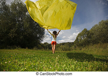 young woman in sunny summer day holds in hand developing on a wind a yellow fabric