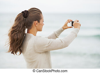 Young woman in sweater on beach taking photo using cell phone