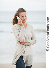 Young woman in sweater on beach talking mobile phone