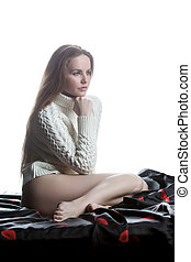 Young woman in sweater sitting on bed