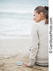 Young woman in sweater with cell phone sitting on lonely beach . rear view