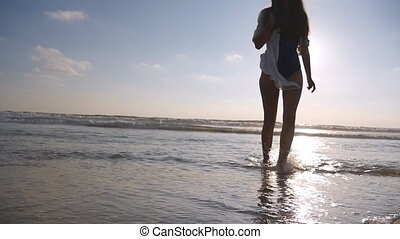 Young woman in swimsuit and shirt going along ocean beach at sunset. Girl enjoying summer. Female walking on the water at the sea shore. Slow motion Close up