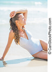 Young woman in swimsuit enjoying sitting at seaside