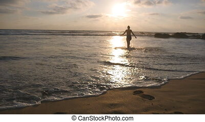 Young woman in swimsuit goes on sea beach to bathe at sunset. Beautiful young girl walking on shore to the ocean during vacation. Relax on summer holiday. Rear back view Slow motion