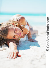 Young woman in swimsuit relaxing on beach