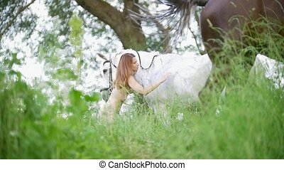 Young woman in swimsuit stroking a white horse outdoors,...