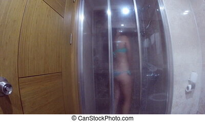 Young woman in swimsuit taking a shower. Beautiful girl is...