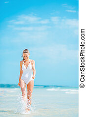 Young woman in swimsuit walking at seaside