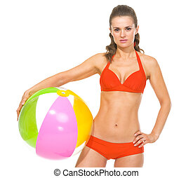 Young woman in swimsuit with beach ball