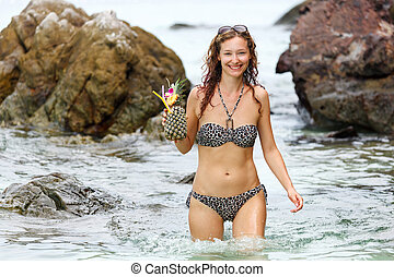 Young woman in swimsuit with cocktail