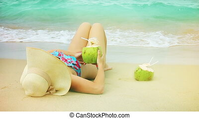 Young woman in swimsuit with coconut cocktail on the beach.