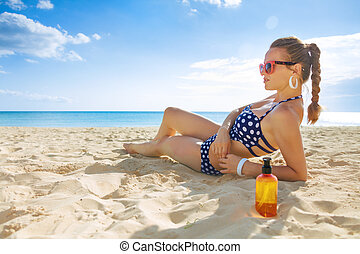 young woman in swimwear on seacoast sunbathing