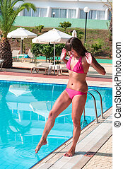 Young woman in swimwear touching cold water in pool by leg