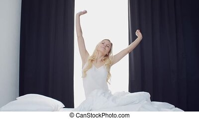 Young woman in the bed. Beautiful blond girl wakes up. ...