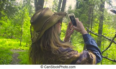 Young woman in the forest taking pictures
