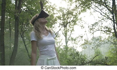 Young woman in the forest uses VR virtual reality glasses and is amazed by nature