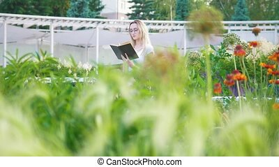 Young woman in the garden with flowers sitting on the bench reading a book