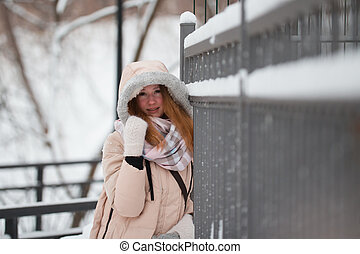 Young woman in the hood stands at snow-covered winter park near metal fence