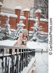 Young woman in the hood stands on bridge at snow-covered winter park near metal fence