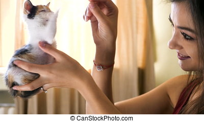 Young woman in the living room playing with her little red with black kitten