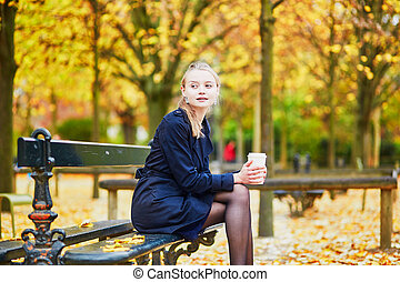 Young woman in the Luxembourg garden of Paris on a fall day