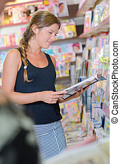 young woman in the magazine shop