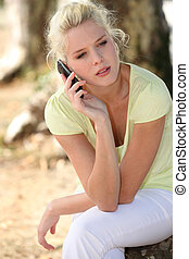 young woman in the park speaking on her cell phone