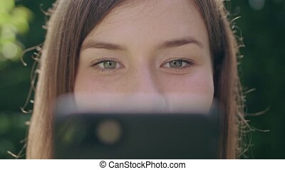 Young Woman in the Park Using a Phone