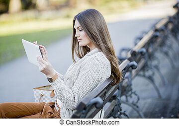 Young woman in the park with tablet
