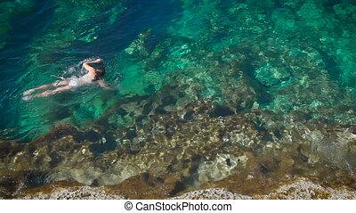 Young woman in the white bikini swimming in beautiful azure sea