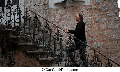 Young woman in torn jeans up the a metal ladder from the stone house.
