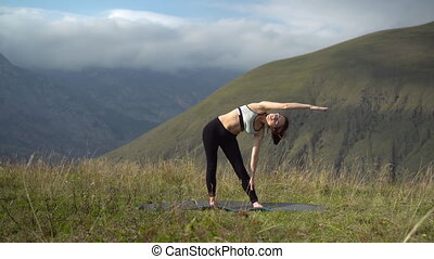 Young woman in tracksuit is engaged in yoga performing triconasana pose in the mountains. The camera moves to create a parallax effect. 4k