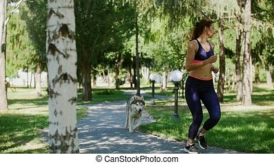 Young woman in tracksuit jogging in the park with husky dog
