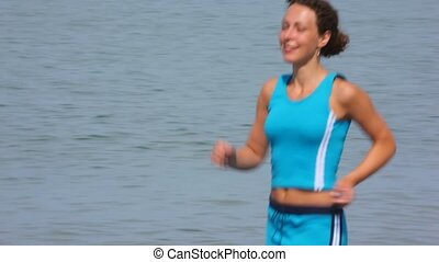 young woman in tracksuit running on pebble beach, sea in...
