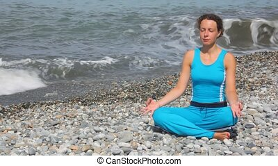 young woman in tracksuit sits in pose of lotus on pebble beach against sea