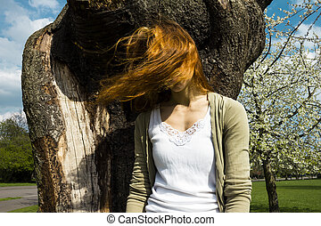 Young woman in tree with windblown hair